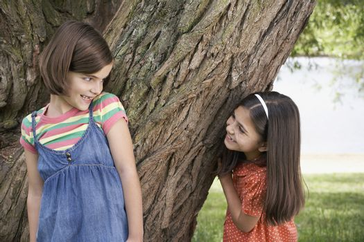 Playful girls playing hide and seek by tree