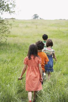 Rear view of children walking in a row on grassy field
