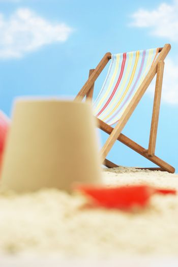 Deck chair behind and castle on beach
