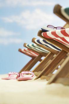 Row of deck chairs on beach focus on flip-flops on ground