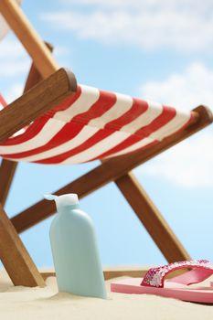 Bottle of cream lotion under deckchair on beach