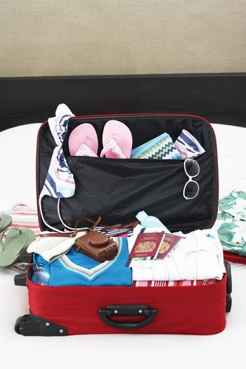 Open suitcase on bed elevated view