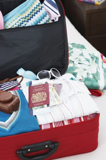 Open suitcase on bed elevated view close up