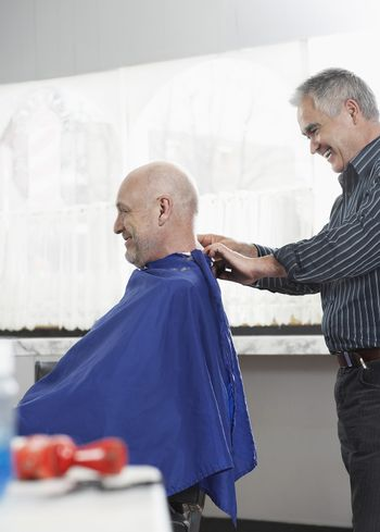 Hairdresser removing cape from senior man after haircut in barbershop