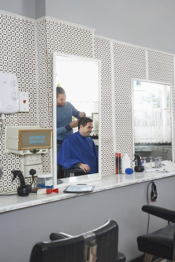 Happy businessman getting haircut from hairdresser at salon