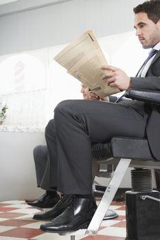 Businessman reading newspaper while waiting for haircut in hair salon