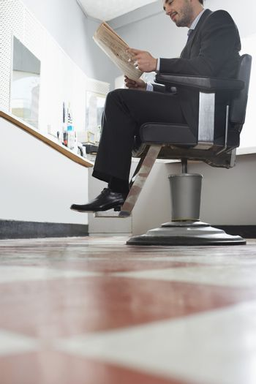 Business man reading newspaper in barber shop