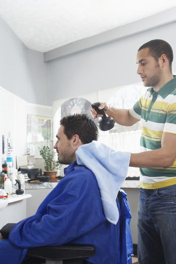 Young hairdresser preparing man for haircut in barber shop