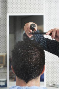 Closeup of hairdresser spraying man's hair in barber shop