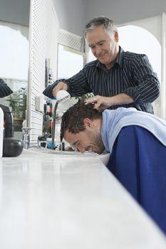 Senior barber washing man's head in hair salon