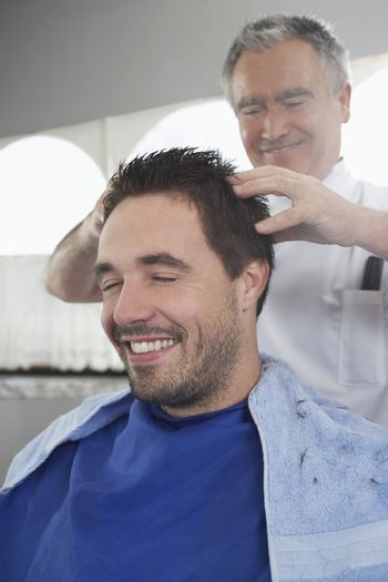 Happy man getting a head massage from hairdresser after haircut
