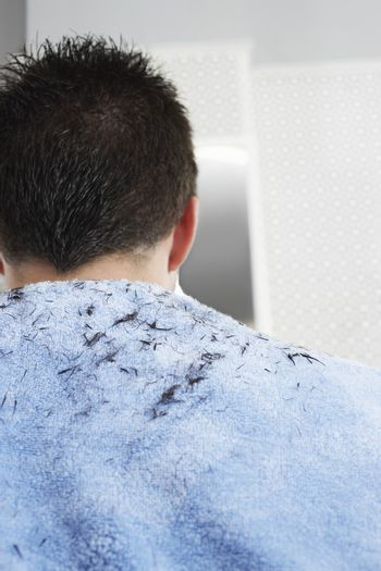Hair clippings on man's back after haircut at barbershop