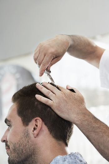 Closeup of man getting an haircut from hairdresser in barber shop
