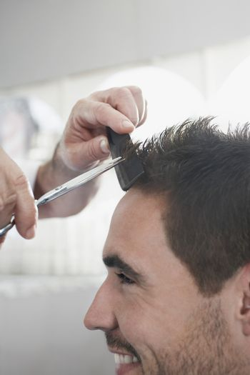 Closeup of smiling man getting an haircut from barber