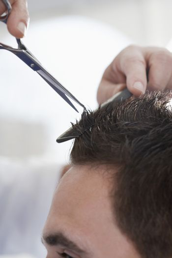 Closeup of man getting an haircut from barber in salon