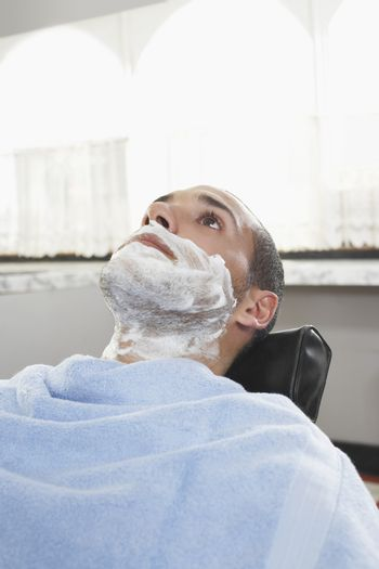 Young man with shaving foam on face at barbershop