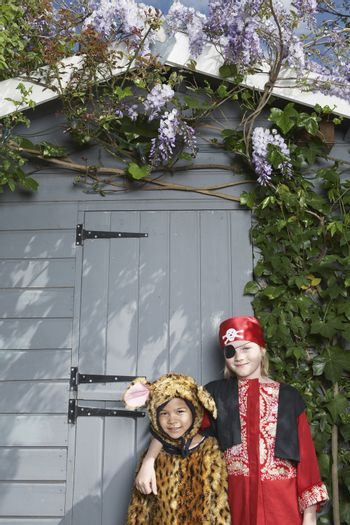 Portrait of two boys in pirate and jaguar costumes standing against shed