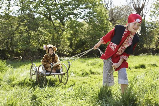Young boy in pirate costume pulling smiling boy in jaguar costume on cart in the garden
