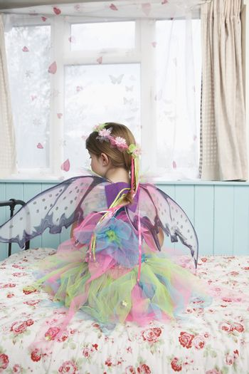 Rear view of a young girl in fairy costume sitting on bed looking through window