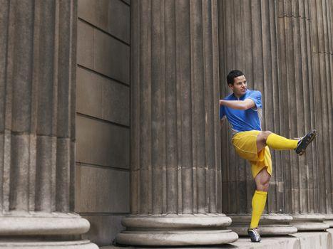 Full length of a soccer player kicking ball between columns
