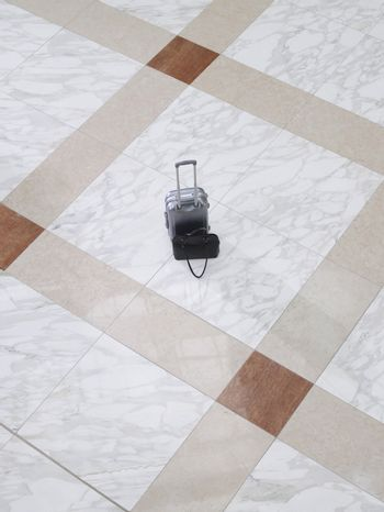 Elevated view of a suitcase and handbag on tiled floor