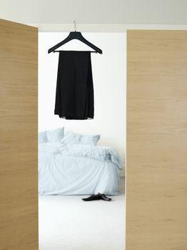 Black dress on hanger in doorway of bedroom at home