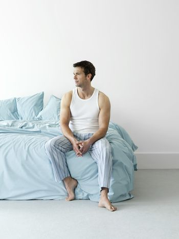 Full length of a thoughtful young man in nightwear sitting in bed