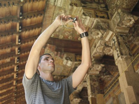 Young man taking photograph of wooden detail of temple