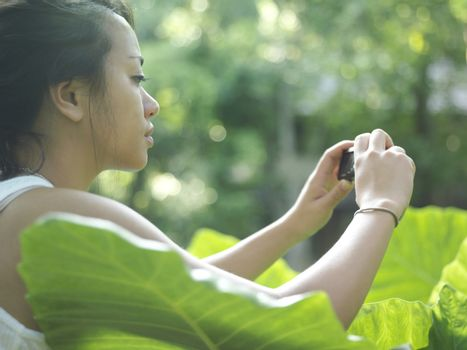 Closeup side view of a young woman taking photograph of leaves