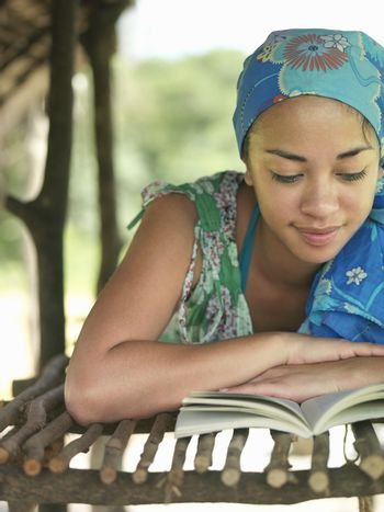 Young mixed race woman lying and reading book in hut
