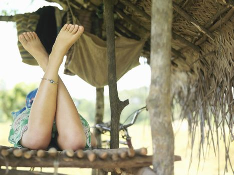 Rear view of a woman lying in hut with bare legs crossed