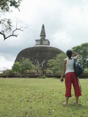 Full length rear view of a young female tourist looking at stupa