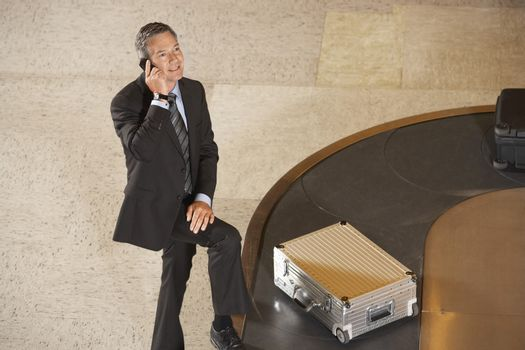 Businessman using mobile phone by luggage on carousel in airport