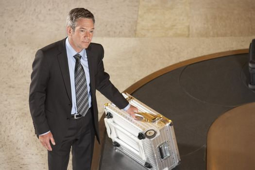 Serious businessman with suitcase at luggage carousel in airport