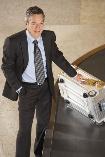 Smiling businessman with suitcase at luggage carousel in airport