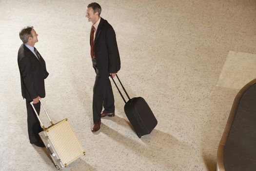 Elevated view of two businessmen with suitcases by luggage carousel in airport lobby
