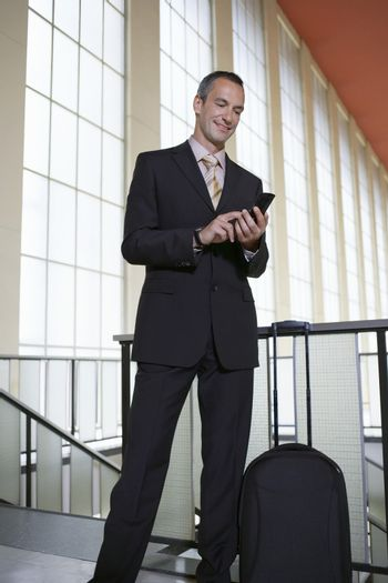 Businessman sending text message in the airport
