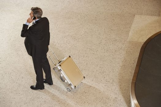 Elevated full length view of a businessman with suitcase using cellphone by luggage carousel in airport