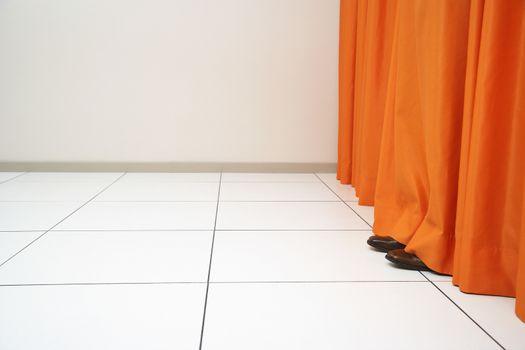 Person hiding behind orange curtain