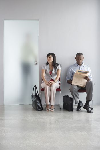 Full length of a young man and woman waiting on chairs by open door in office corridor
