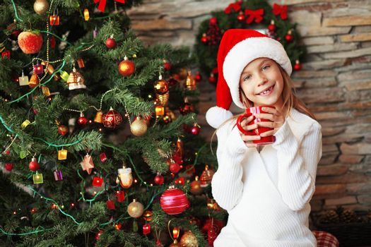 Portrait of a child drinking hot tea near Christmas tree