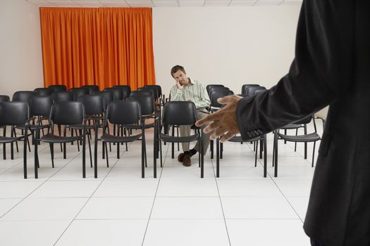 Single male executive listening to a seminar in conference room