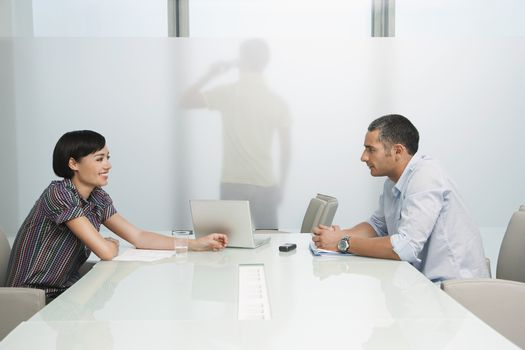 Side view of a man and smiling woman talk over conference table with man on cellphone across translucent office wall