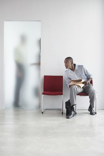 Young man listening to two people talk behind translucent door in office