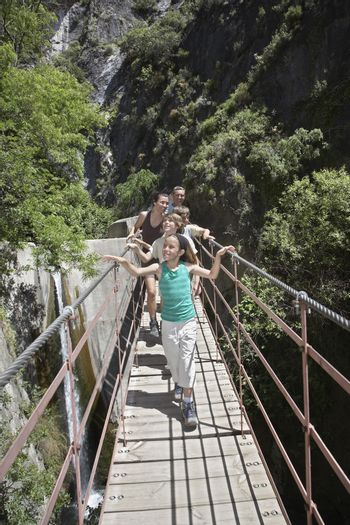 Couple with three children crossing bridge in mountains