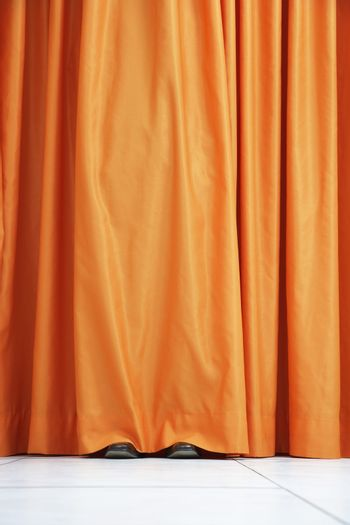View of shoes seen hiding behind orange curtain