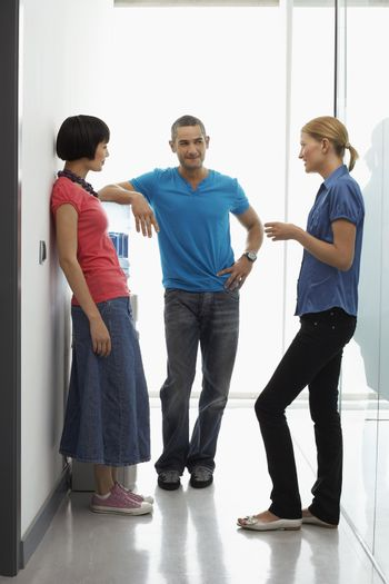 Full length of three office workers talking by water cooler in hallway