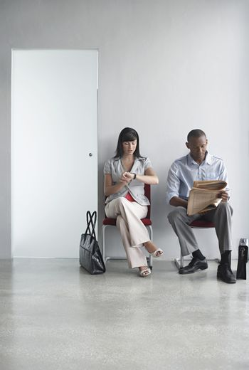 Full length of a young man and woman sitting on chairs in office corridor