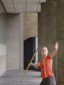 Woman throwing javelin outside building