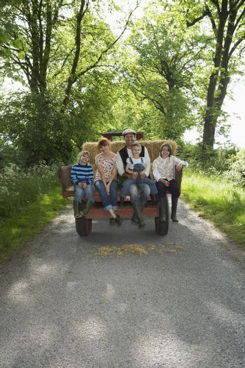 Parents with three children (5-9) sitting on trailer on country lane